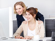 Two business women surching on the internet in the office