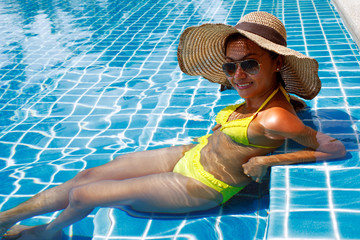 Young woman in a yellow swimsuit seating down in a swimming pool
