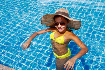 Young woman in a yellow swimsuit standing up in a swimming pool
