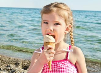 Little girl eating ice cream on beach vacation