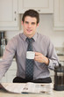 Man reading newspaper while drinking coffee