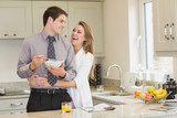 Woman hugging her husband while eating cereal