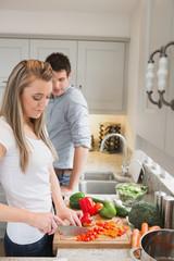 Woman enjoying cooking with man watching