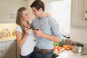 Couple in the kitchen drinking a glass of red wine
