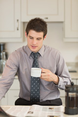 Man turning the page while drinking coffee