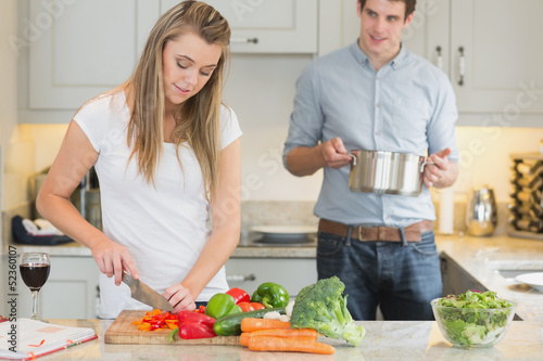 Man helping woman with cooking