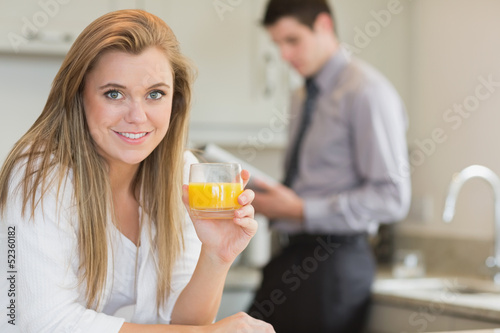 Young woman drinking orange juice in kitchen