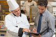 Head chef and waiter discussing menu