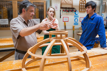 Two students and an explaining teacher in a woodwork class