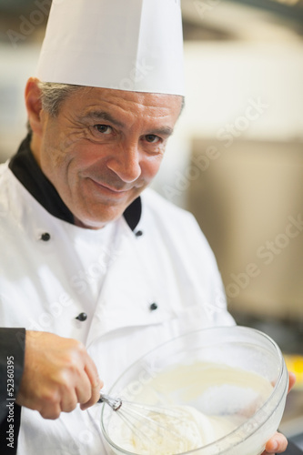 Smiling chef whisking cream