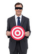 Blindfolded and smiling businessman holding a red target