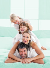 Smiling family piled on top of dad