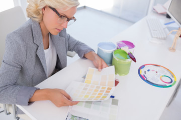 Concentrated blonde interior designer holding colour charts