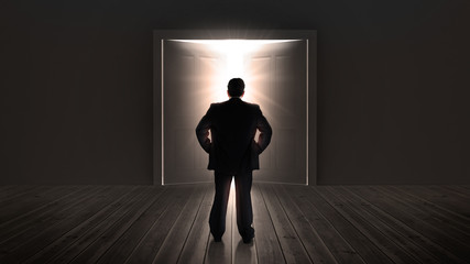Businessman watching doors opening to a bright light