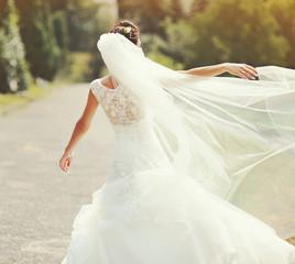 happy brunette bride spinning around with veil