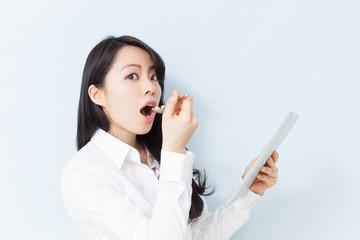 タブレットPCを見ながらサプリメントを食べる女性