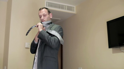 Young businessman ties necktie in a hotel room