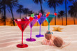 colorful cocktail in a row cherry on sand palm trees