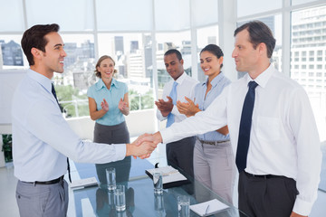 Smiling business people shaking their hands