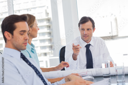 Businessman pointing someone while talking to colleagues