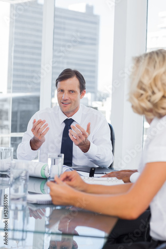 Businessman gesturing while talking to colleagues
