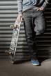 Skater standing against metal shutters