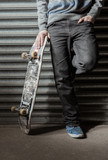 Skater standing against metal shutters