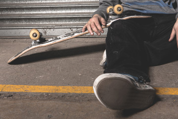 Skater sitting on ground with board