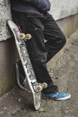 Skater leaning against wall with his board