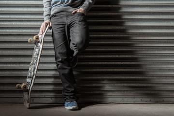 Skater leaning against metal shutters