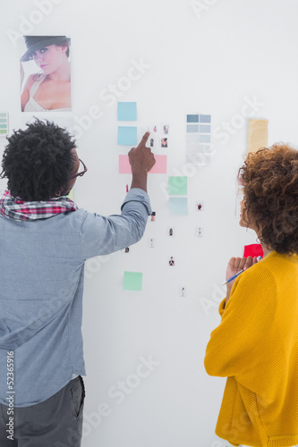 Designers pointing at a group of photos