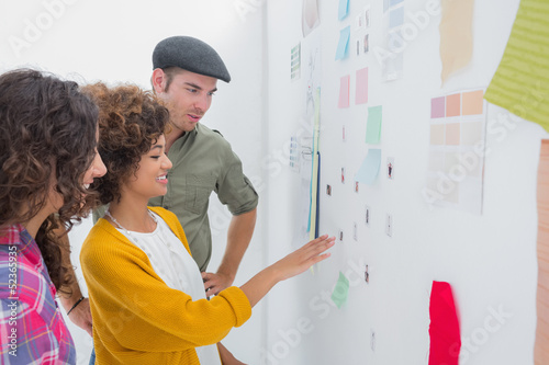 Smiling team of designers working together and pointing at a wall