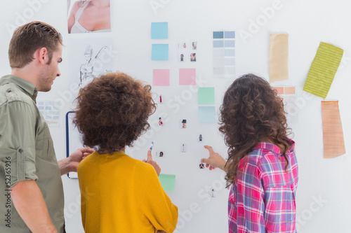 Team of designers working together and pointing at a wall