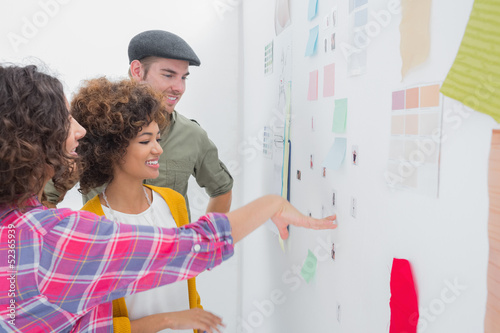 Young team of designers working together and pointing at a wall