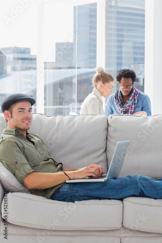 Cheerful worker using his laptop while laying on a couch