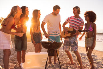 Group of friends playing guitar on the beach