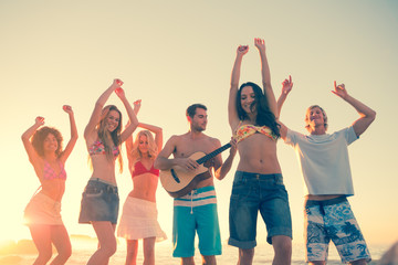 Group of friends having fun on the beach and playing guitar