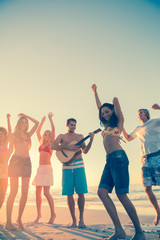 Friends dancing and having fun on the beach