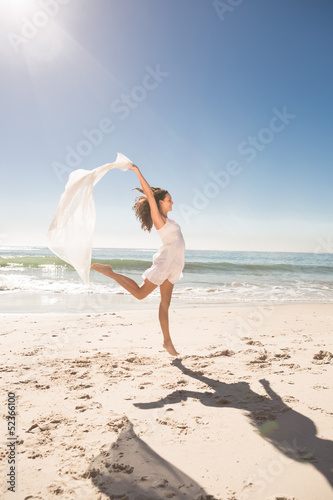 Pretty young woman jumping on the beach