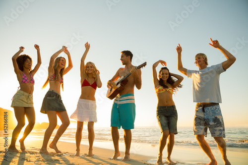 Friends having a party and playing guitar on the beach
