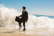 Businessman walking at the edge of the sea
