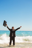 Businessman in the sea raising his arms
