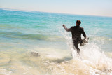 Businessman running into the sea