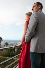 Delighted couple standing on the balcony