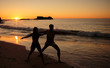 Silhouettes of people practicing yoga on the evening
