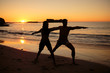 Silhouettes of people practicing yoga under the sunset