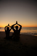 Silhouettes of people practicing yoga sat on the sand