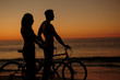 Silhouettes of couple biking together on the beach