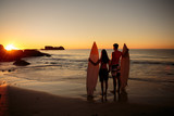 Lovers hand in hand with surfboards looking at the sunset