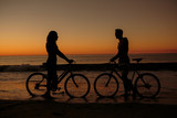 Silhouettes of people facing each other on bicycles
